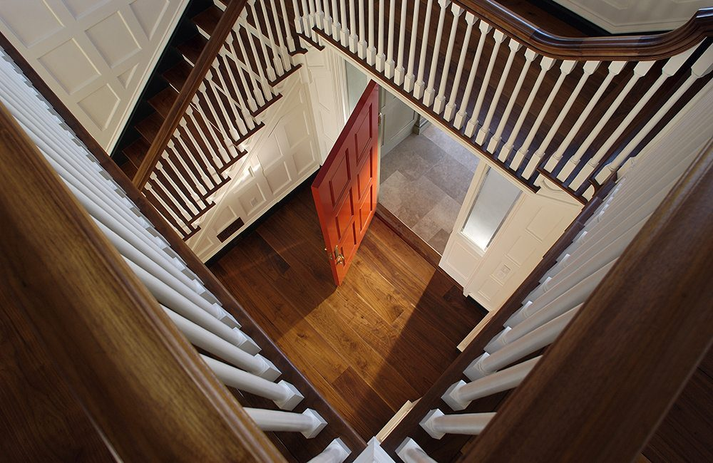 Looking down a beautiful staircase, with warm toned wood and painted white accents