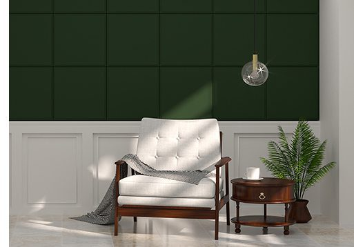 White armchair in front of green wall white lamp and sideboard